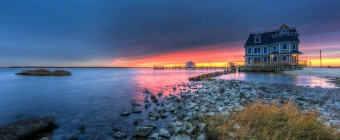 An HDR sunset of Antoinetta's Restaurant on Cedar Run Dock Road in Manahawkin, NJ. While grays and blues set the tone of this seascape, the fire lit sunset in the distance elevates the drama with strong reds and pinks.