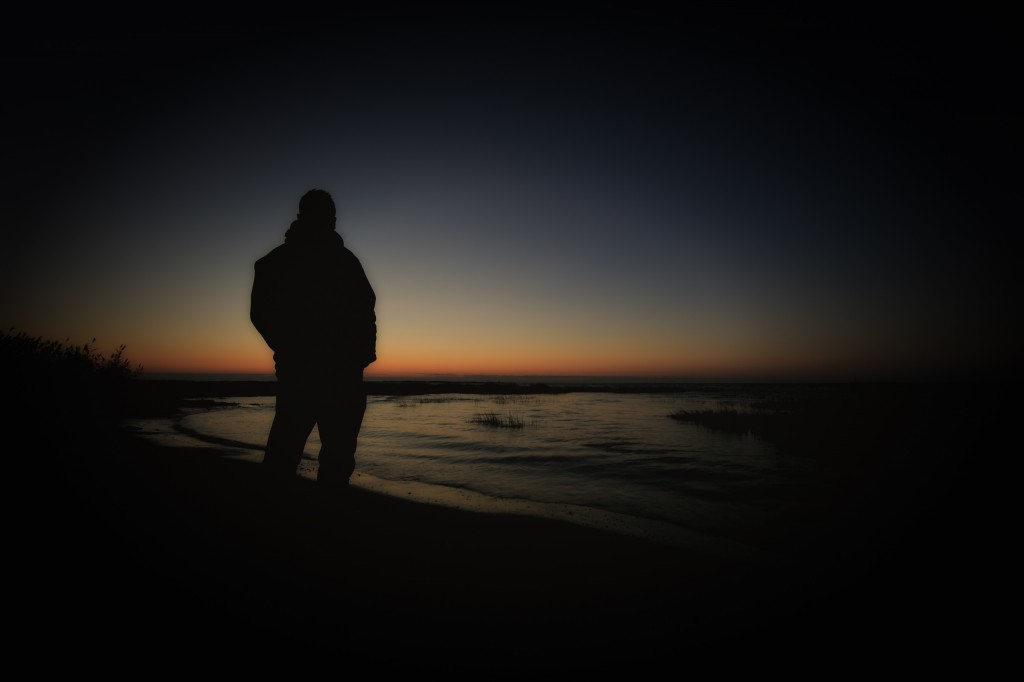 A silhouette self-portrait of Greg Molyneux watching a late Fall sunrise