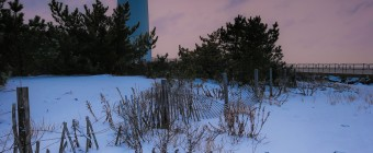 A portrait orientation HDR photograph of the Barnegat Lighthouse at sunset in snow.