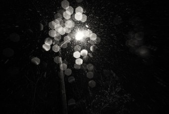 A black and white abstract photograph of a street light with falling snow. Shot with plentiful bokeh in a film noir style. Taken by Manahawkin, NJ, photographer Greg Molyneux.