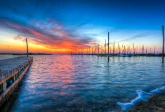 An HDR photograph of a Great Bay Boulevard sunset by Manahawkin, NJ, photographer Greg Molyneux. In this photograph the sun sets next to an abandoned boat dock.