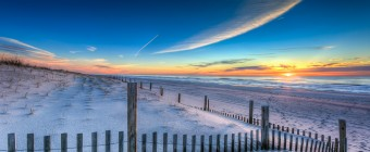 An HDR sunrise photograph overlooking the dunes, dune fence, ocean and sand of 13th Street in Ship Bottom, NJ.
