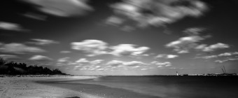 An afternoon long exposure photograph taken from High Bar Harbor in Barnegat Light overlooking east toward the Barnegat Lighthouse. In this empty bay beach scene, the low level clouds streak across this black and white photograph from left to right.