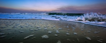 A ground level perspective wide angle photograph of an ocean break during blue hour in Ship Bottom, NJ, on Long Beach Island. Foreground bubbles are left behind the retreating waves.