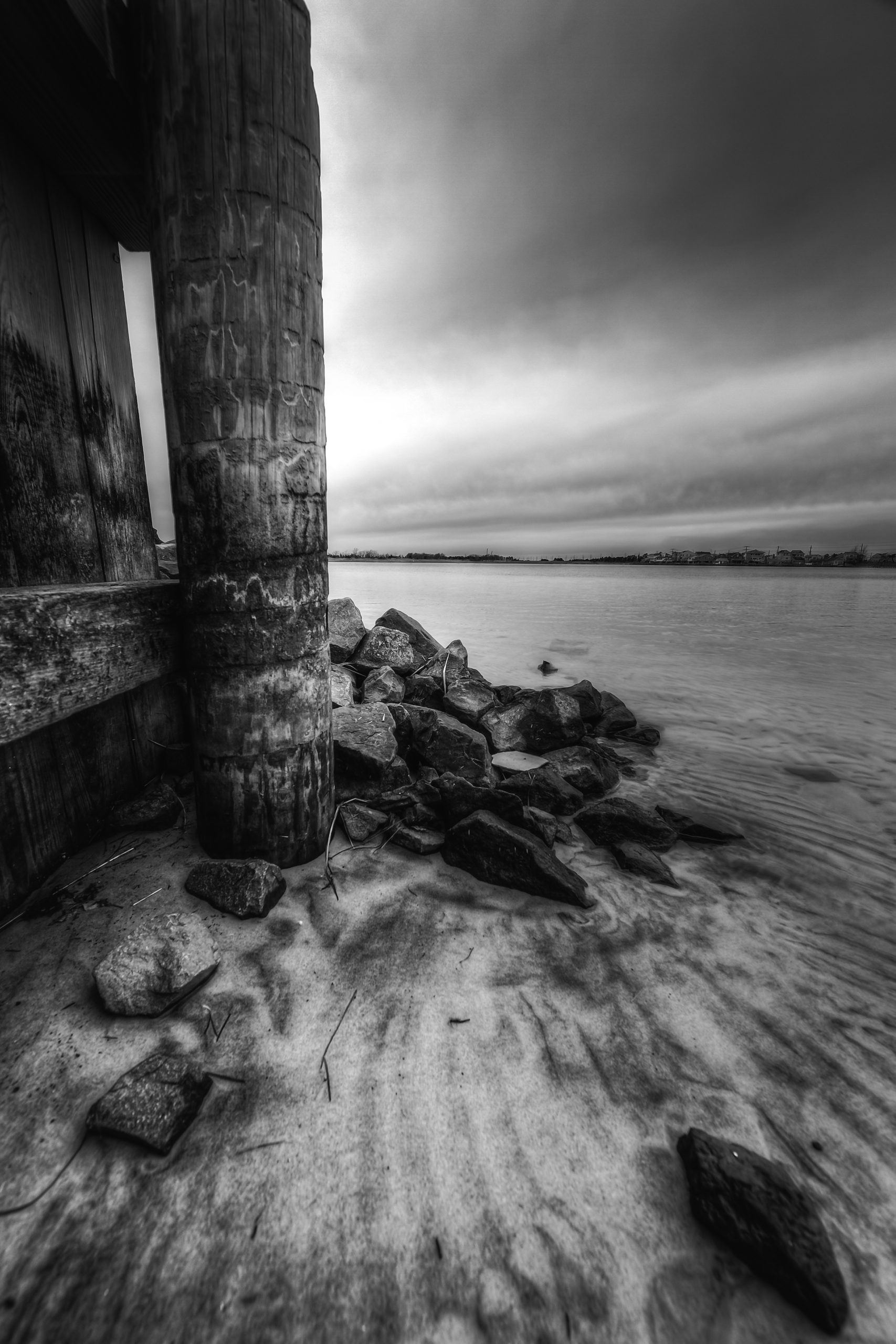 A seven frame black and white composite exposure of a wooden bulkhead and mounded jetty rock