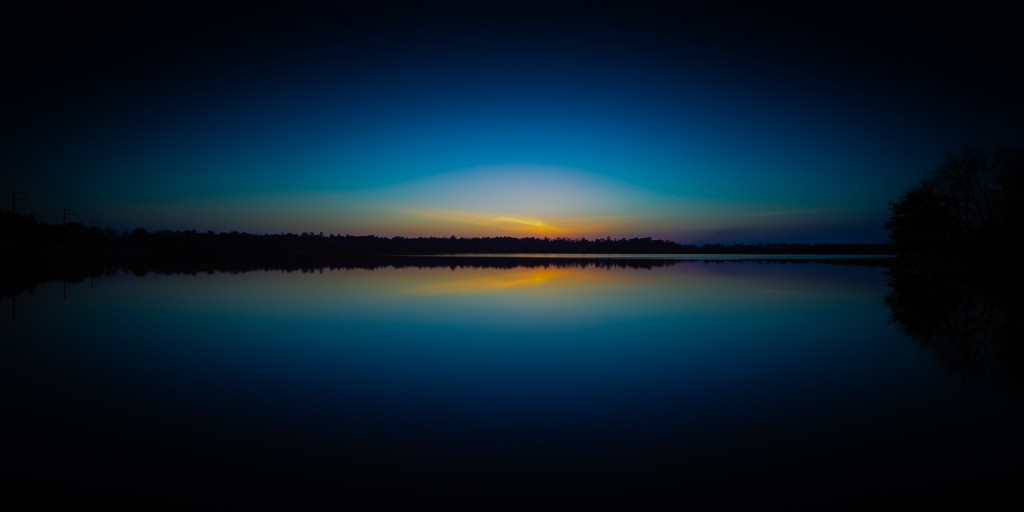 A long exposure photograph taken during blue hour overlooking the lake at Stafford Forge Wildlife Management Area. The picture creates a near perfect mirrored reflection.