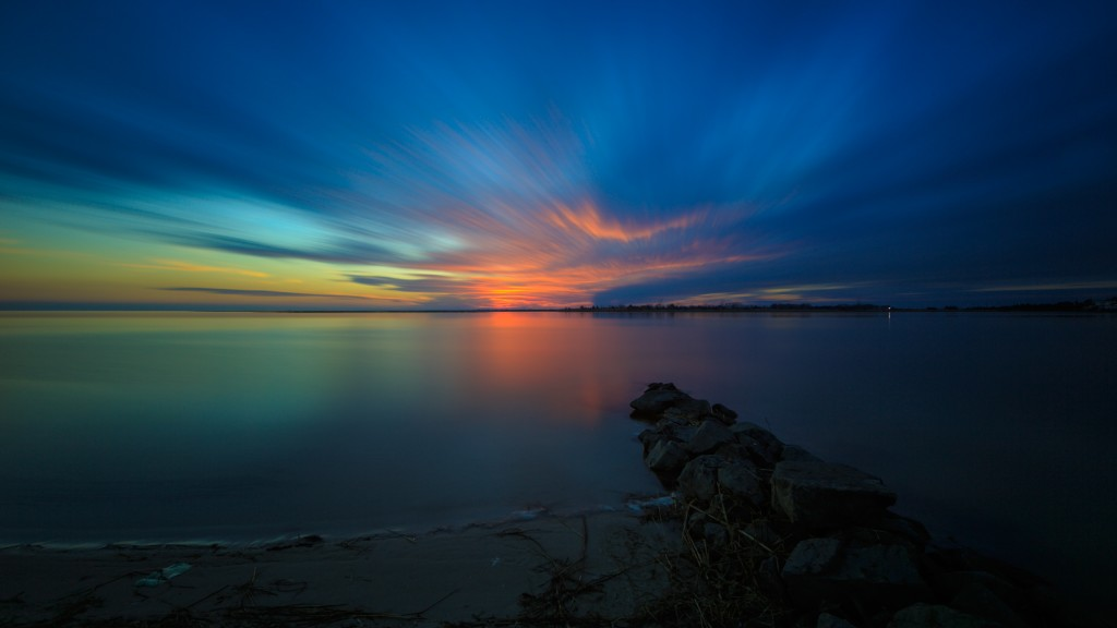 A long exposure photograph taken during blue hour overlooking Barnegat Bay from a sunset park in Ship Bottom, New Jersey. A stretch of jetty rock serves as the foreground.