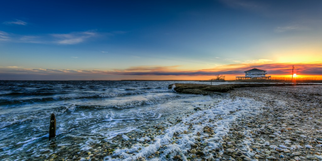 An HDR photograph taken at sunset from the east end of Cedar Run Dock Road. Rolling waves from Barnegat Bay move onshore leaving heavy foam upon the small shell-laden beachfront.