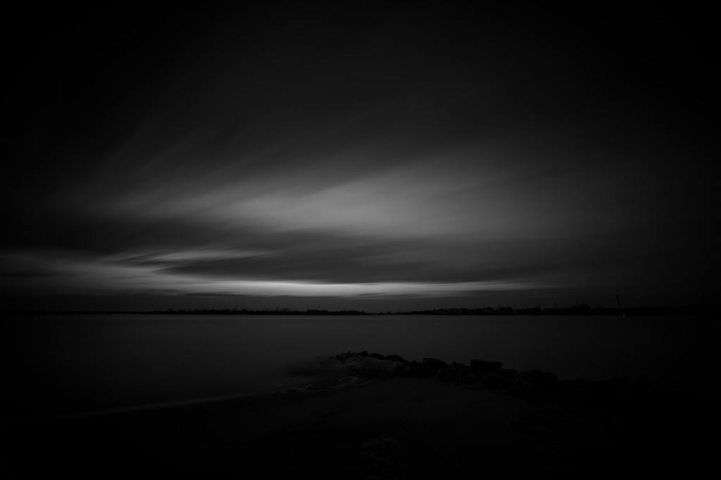 A low key long exposure black and white photograph taken over Barnegat Bay from Sunset Point in Ship Bottom, New Jersey. This photograph is marked by dark tones and strong contrast across the horizon.