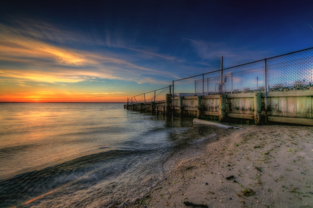 HDR photograph taken just before sunset at Sunset Park in Surf City, New Jersey. This photograph features a bulkhead capped by fence and fiery sunset colors over Barnegat Bay.