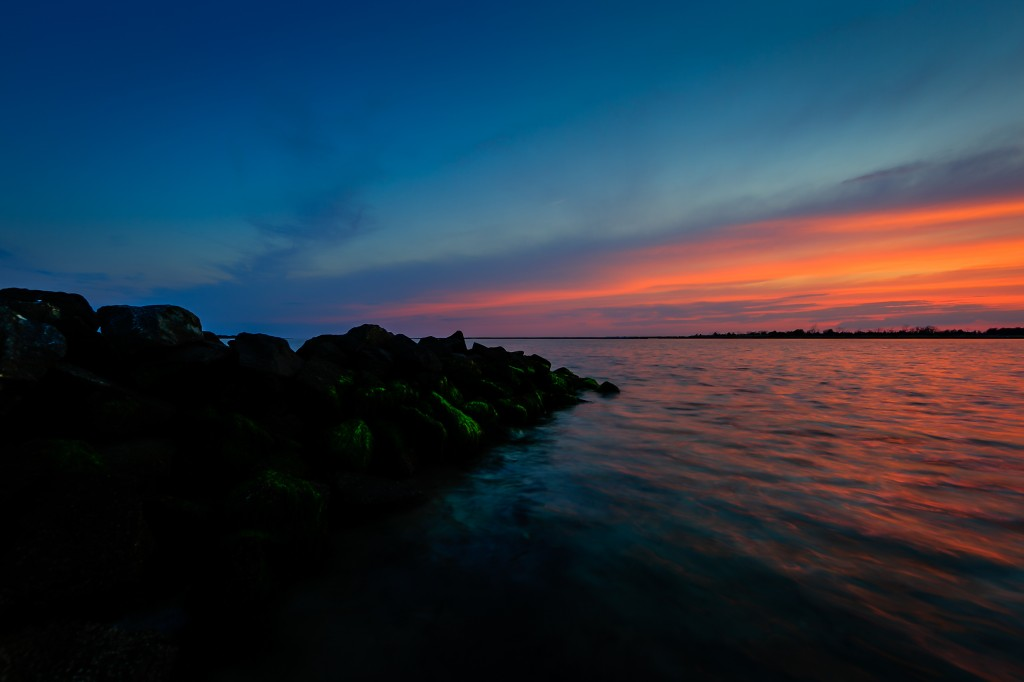 An HDR photograph taken at sunset from along the jetty at Sunset Point in Ship Bottom, New Jersey. The in water perspective hugs the darkened jetty rock and frames the colored sky and water.