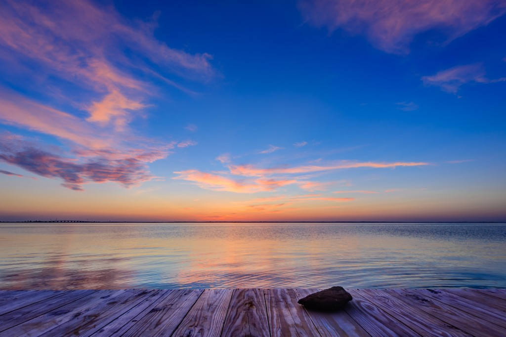 A late evening HDR photograph taken just after sunset from Sunset Park in Surf City, New Jersey. The exposure looks out over a very calm Barnegat Bay and features the unfinished wood of the dock at the edge of the park with a small stone in the foreground.