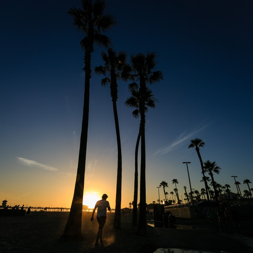 A sunset photograph taken during peak summer at the Huntington Beach, California, pier. A young man kicks up dust as he walks between palm trees with beautiful twilight approaching.