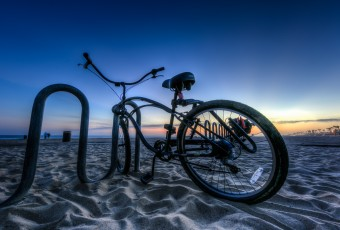 An HDR photograph taken just after sunset during blue hour along the shores of Huntington Beach California. The foreground is marked by a sweet beach cruiser bicycle locked to a beach bound bike rack. The Pacific Coast Highway lies away in the distance.