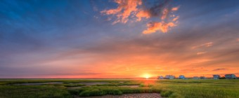 A subtle lens flare sends a rich golden glow across the lush green salt marsh in this stunning HDR sunset photograph.
