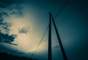 Cross processed with Trey Ratcliff's 'The Navigator' Adobe Lightroom preset, this wide angle photograph features telephone lines backdropped by a dramatic sky, all in a blue monochrome treatment.