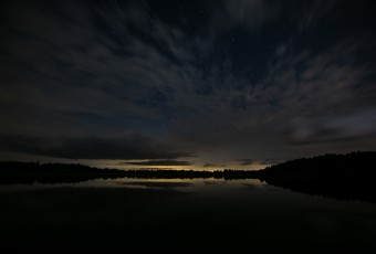 A long exposure wide angle landscape photograph taken at night just in front of the lake at Stafford Forge Wildlife Management Area. Low clouds race across a sky that's back-dropped with stars.