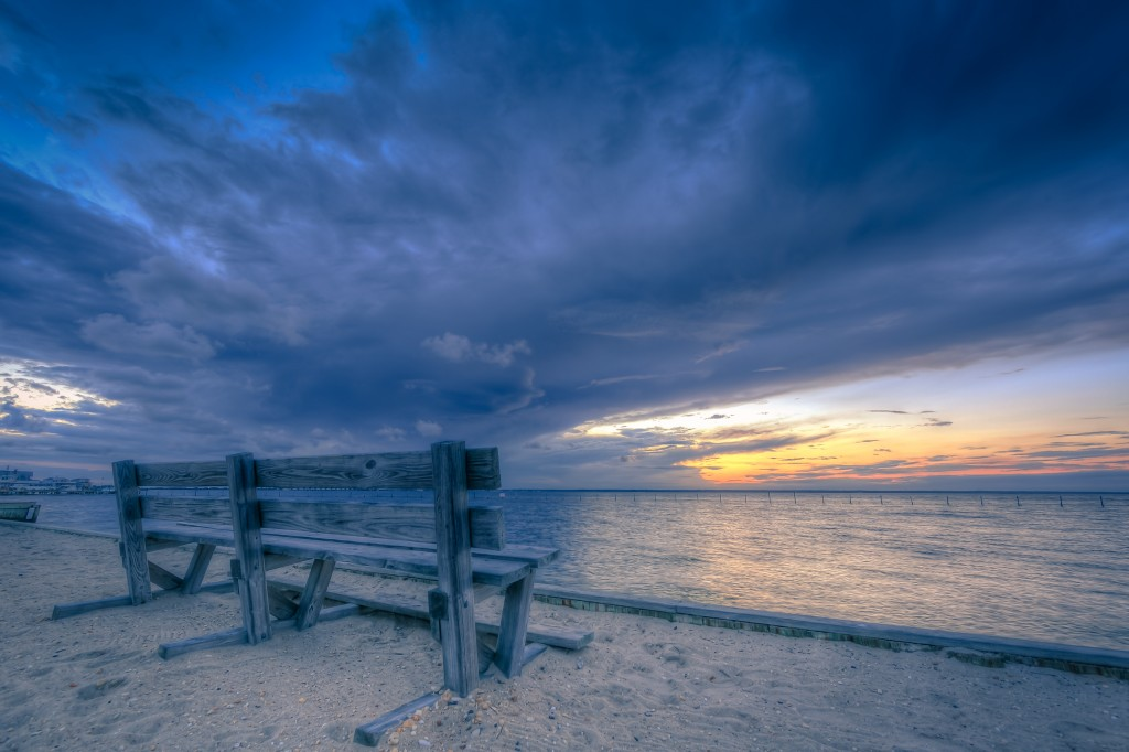 A cross processed wide angle HDR landscape photograph of a park bench, beach sand, and Barnegat Bay just at sunset. Dramatic clouds dominate the sky and a cool blue tone brings a real calming influence to the image.