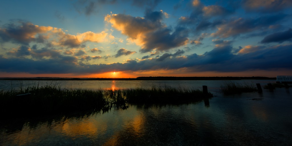 A low key HDR sunset photograph overlooking the tidal overflow of a lagoon flowing through a salt marsh.
