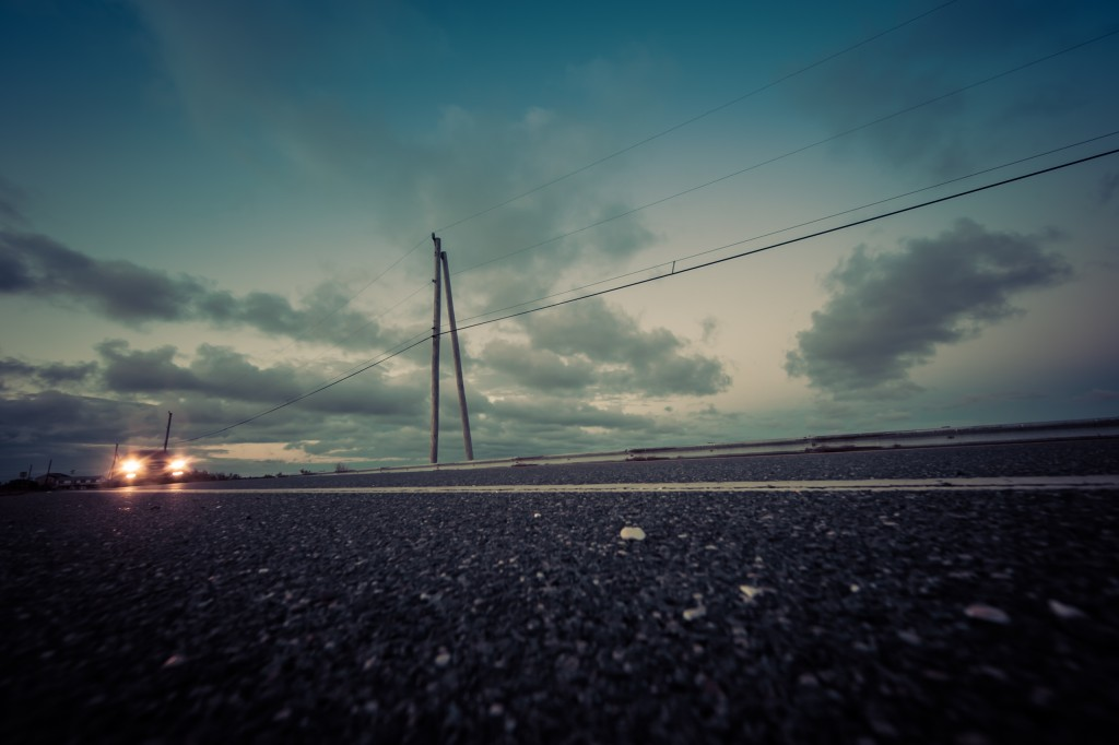 A cross processed street level photograph of a lone car approaching, headlights on. Power lines and clouds mark the background