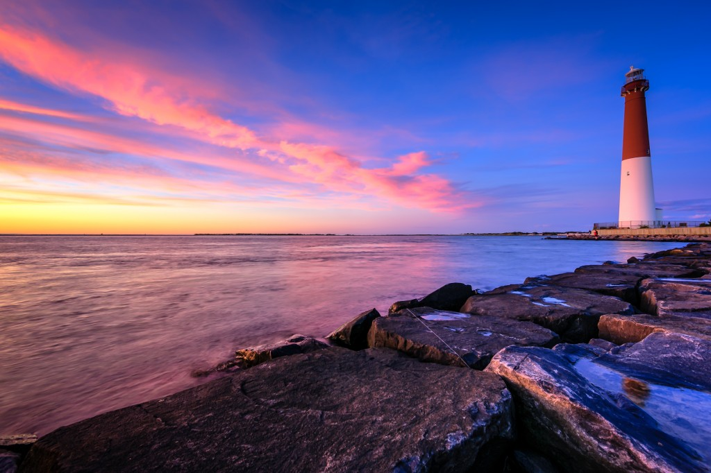 An HDR photograph of Barnegat Lighthouse taken from the jetty rock at blue hour overlooking majestic pastel clouds over Barnegat Bay.