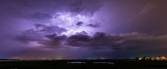 Long exposure lightning photography taken from Cedar Run Dock Road. Cloud to cloud lightning ignites the sky in an electrified purple glow.
