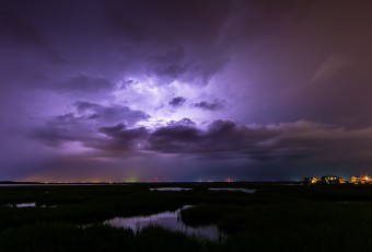 Long exposure lightning photography taken from Cedar Run Dock Road. Cloud to cloud lightning ignites the sky in an electrified purple glow.