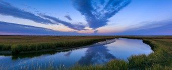 A blue hour photograph of Dock Road's north marsh on a calm Fall evening. No wind allowed a glassy reflection on the marsh estuary, mirroring the clouds