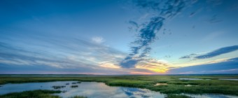 Blue hour in HDR. Taken over Dock Road's southern marsh just after sunset, this photograph features soft tones, cool blues, and understated clouds