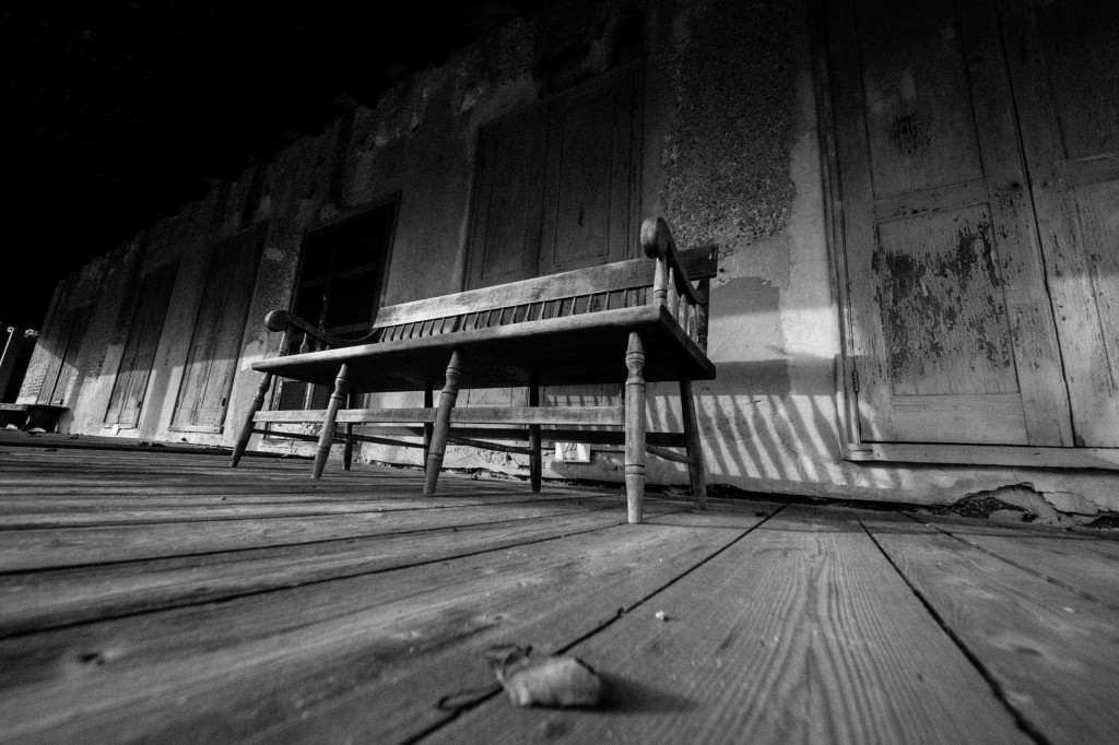 In this black and white photograph, strong leading lines move the eye through this olde tyme porch where an old wood bench sat steady for a lifetime of stories, friendship and support.
