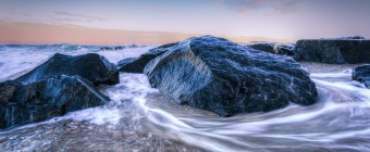 In this seascape photograph, Atlantic Ocean tidal waters ebb and flow as seawater races around jetty rock as gravity pulls the water back to the sea