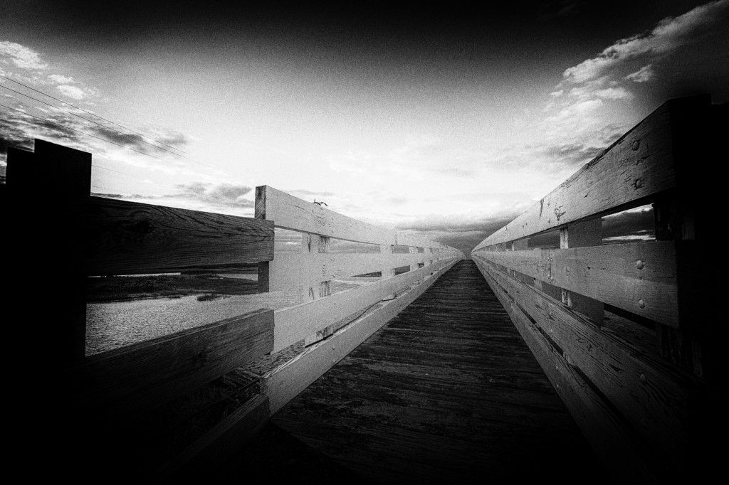 A gritty, grainy black and white wide angle photograph of a wooden pedestrian path along an old bridge spanning the Great Bay Boulevard salt marsh