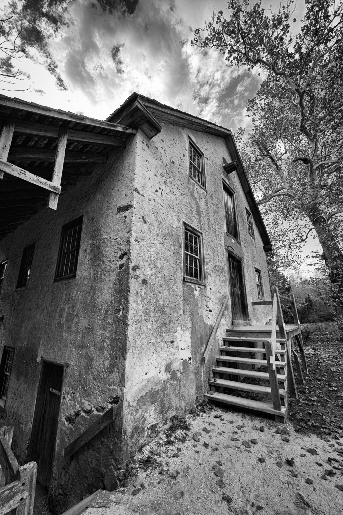 A wide angle black and white photograph of the old Batsto Village gristmill taken in portrait orientation