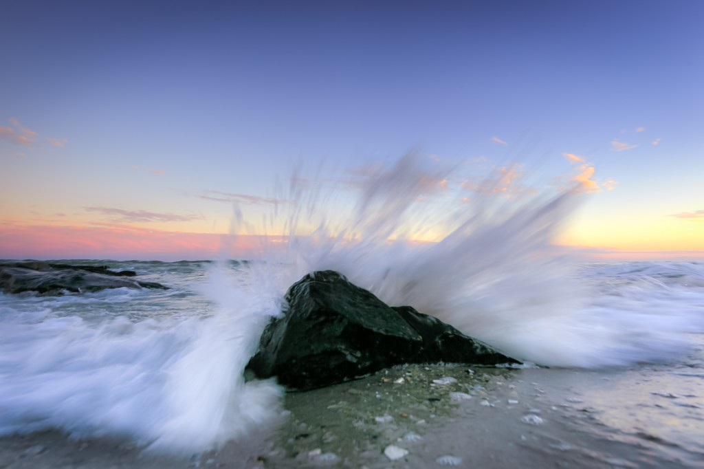 A blue hour photograph featuring ocean spray bursting behind a lone foreground jetty rock sending water in all directions