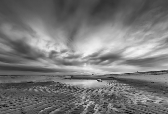 A black and white HDR photograph of fierce clouds, a tidal pool and undulating sands on the beach in Holgate, NJ.