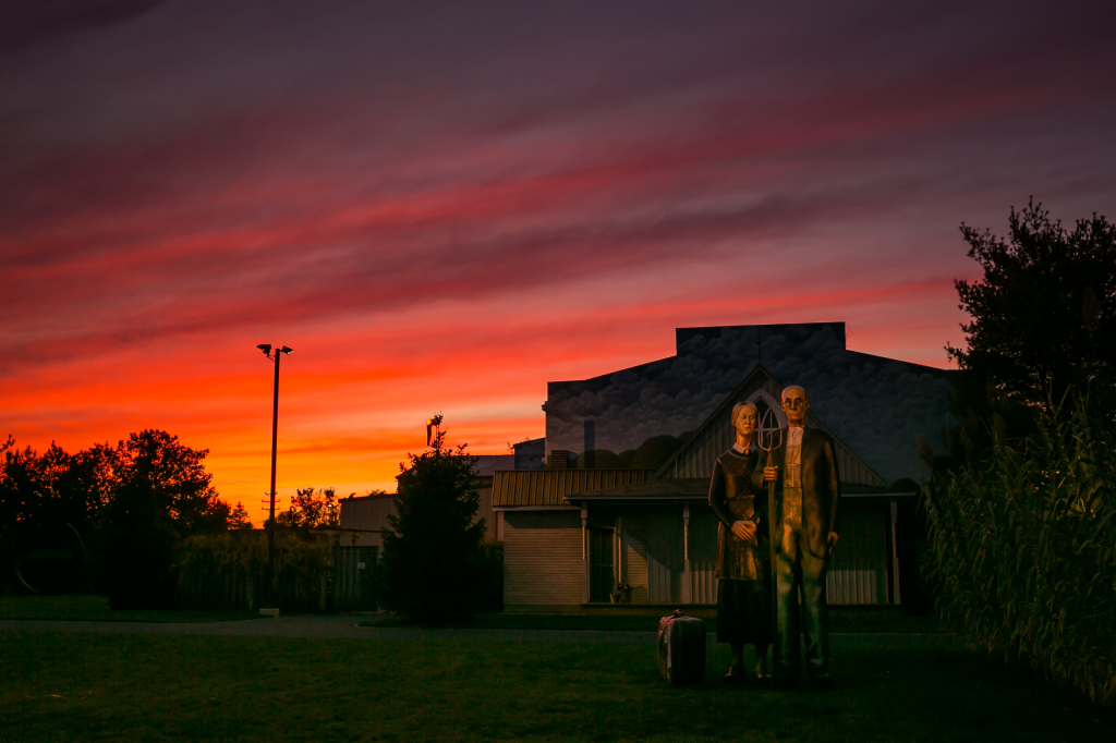 A photograph of a fiery sunset backlighting the American Gothic display at New Jersey's Grounds for Sculpture. True to the look of the original painting, here the famous farmers are depicted in larger than life cast bronze statuary.