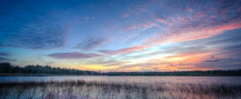 A subtle HDR sunset photograph with soft yellows and a touch of pink marking the racing clouds. Taken at the Stafford Forge Wildlife Management Area.
