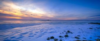 An HDR sunset photograph taken from Harvey Cedars Sunset Part of a fully frozen Barnegat Bay. Unique ice patterns and strewn jetty rock mark the picture's foreground.