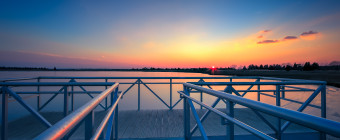 An HDR sunset photograph taken from the aluminum dock overlooking Bass River in New Gretna, New Jersey. With the metal dock marking the foreground, a rich pastel glow colors the sky and water on this near cloudless evening.