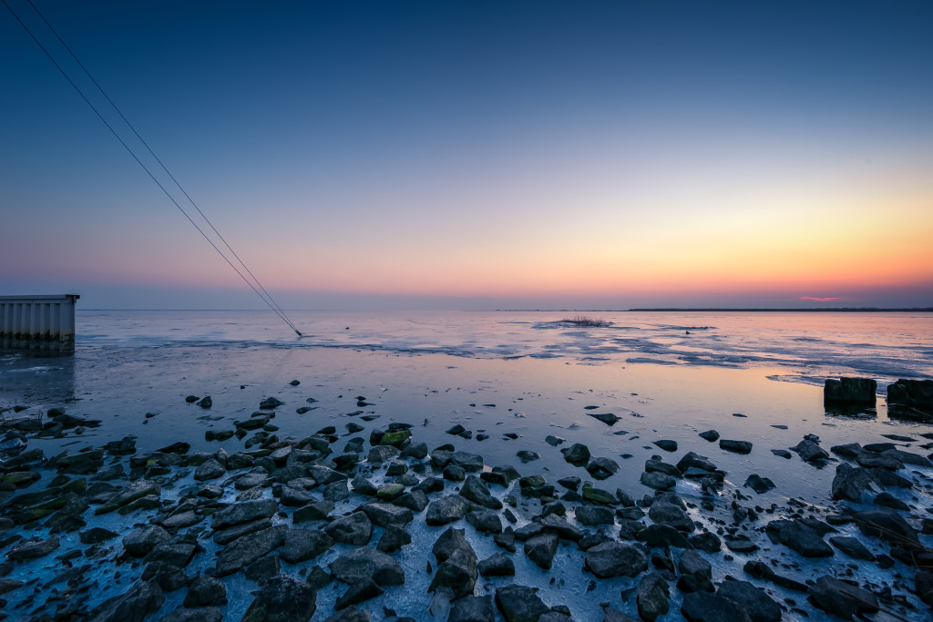 An HDR blue hour photograph of a stony bayshore mixed with thin sea ice in the foreground and angle guy-wires in the mid ground plunging into the frozen bay.