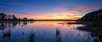 A spectacular HDR photograph taken during blue hour overlooking the front lake at the Stafford Forge Wildlife Management Area. Pastel clouds drape the horizon while marsh grasses are dormant and still in the mirrored reflection of water.