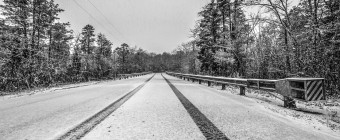 Light snow falls on an empty roadway marked only by a lone set of tire tracks. Flanking the road are guardrails and pine trees to either side of this black and white photograph.