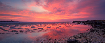 A stunning HDR photograph glistening with pink pastels dancing off the icy stillness of Barnegat Bay as seen from Harvey Cedars Sunset Point.