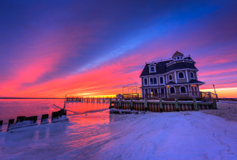 HDR photograph of Antoinetta's Restaurant backdropped by a stunning blue hour over frozen bay and shores.