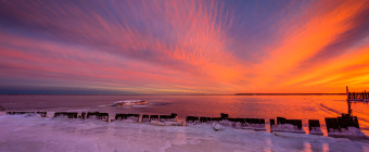 Intense pastels color the undulating clouds in this spectacular HDR sunset photograph over a frozen Barnegat Bay.