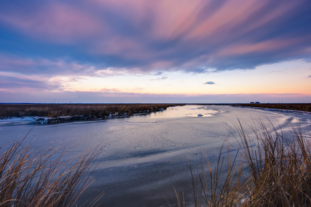 During a break in the weather clouds part just before sunset coloring the clouds purple and pink in this HDR photograph of the marshes of Cedar Run Dock Road.