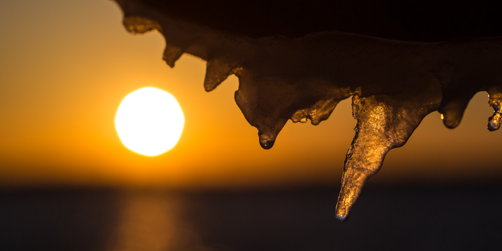 An icy handrail makes for an interesting macro shot with the setting sun over the bay off in the distance left of a sharp focused icicle.