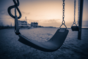Wide angle sepia photograph of two swings over the sand at Surf City Sunset Park