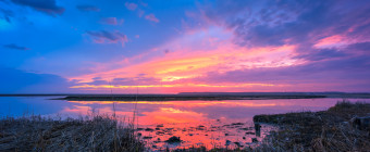 Rain clouds part just after sundown revealing deep blues, pinks, purples and reds in this wide angle HDR sunset photograph taken along the south marsh next to Great Bay Boulevard.