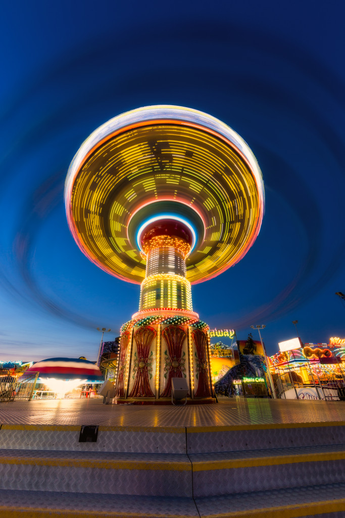 A blue hour long exposure portrait orientation wide angle photograph of Wave Swinger; a carnival swing captured in motion at Casino Pier, Seaside Heights, New Jersey.